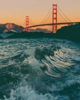 onde dell'oceano che si infrangono in primo piano con il golden gate bridge sullo sfondo foto