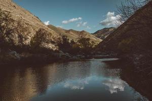 specchio d'acqua tra le montagne durante il giorno