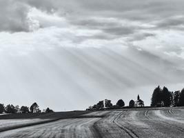 luce del sole che splende sul campo in erba e sul villaggio foto