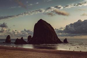 silhouette di pagliaio rock sulla spiaggia di cannone foto