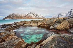 lago blu circondato da montagne sotto nuvole bianche foto