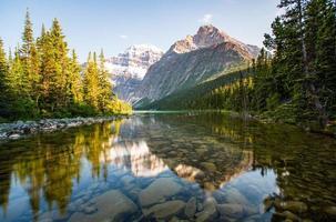 alberi verdi vicino a un lago e montagne innevate foto