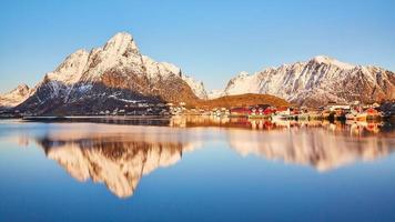 montagna marrone e bianca che riflette vicino a un corpo d'acqua foto