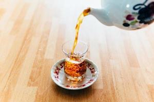 versando il tè nella tazza foto