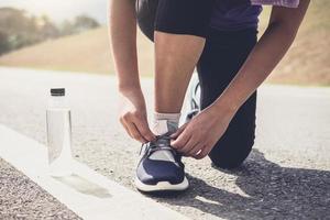 stile di vita sano, corridore che lega le scarpe da corsa che si prepara per la corsa sul concetto di benessere di allenamento di jog della pista di corsa