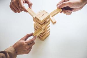 giovane squadra di affari che mette il blocco di legno sulla torre foto