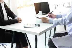 medico e paziente di sesso femminile discutono insieme di documenti in una consultazione foto