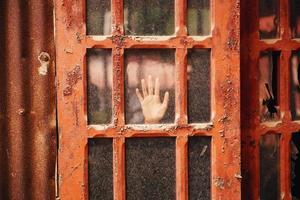 vista di una mano sulla porta con pannelli di vetro