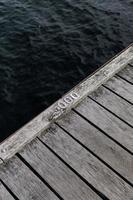 primo piano del bacino di legno vicino all'acqua foto