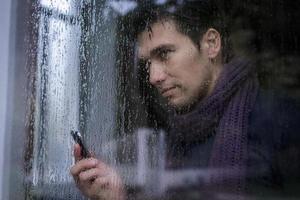 volto dell'uomo che mostra attraverso la finestra bagnata foto