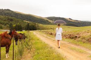 giovane donna che cammina sulla strada della fattoria foto