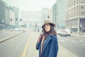 bella giovane bruna in posa per le strade della città foto