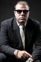 uomo di gangster mafia in vestito con occhiali da sole e cravatta. foto