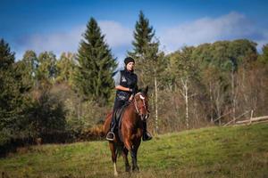 donna attraente elegante che monta un cavallo