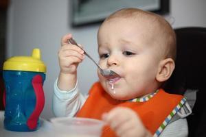 neonato che mangia con un cucchiaio foto