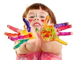 foto del bambino con le mani tese di vernice colorata