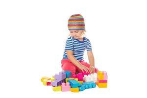 bambina in una maglietta colorata che gioca con il giocattolo da costruzione foto