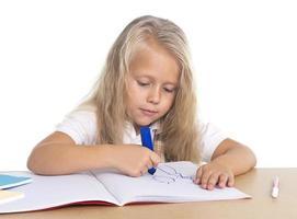 carino schoogirl felice sulla scrivania disegno sul blocco note con pennarello foto