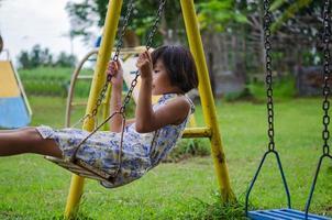 bambino spensierato su un'altalena in un parco foto