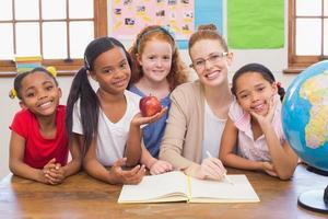 alunni carini e insegnante sorridendo alla telecamera in classe foto