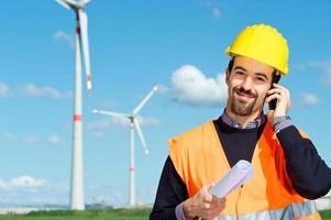ingegnere nella stazione del generatore di energia eolica parla al telefono foto