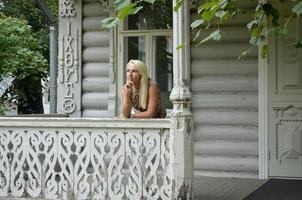 giovane donna sotto il portico di una vecchia casa foto