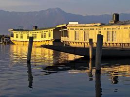 casa barca sull'acqua con vista sulle montagne in lontananza