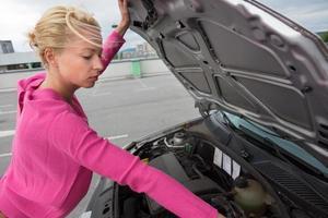 donna che ispeziona il motore di automobile rotto. foto