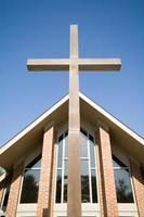 grande croce davanti al cielo blu del tetto della chiesa moderna foto