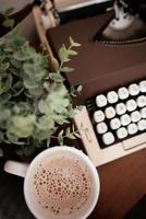 primo piano di una tazza di caffè vicino a una macchina da scrivere e una pianta foto
