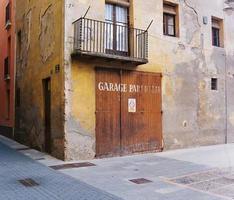 vecchia porta del garage in legno in rovina edificio catalano foto