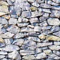 superficie del muro di pietra incrinata con cemento foto