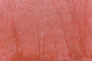 Close up della parete esterna con intonaco decorato di colore rosso foto