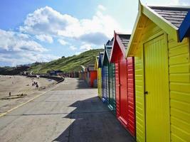 fila di capanne sulla spiaggia colorata a Whitby, nello Yorkshire, Inghilterra. foto