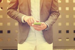 uomo elegante utilizzando il cellulare all'aperto.