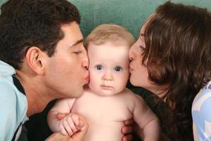 genitori che baciano il bambino foto