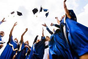 gruppo di giovani laureati felici che gettano cappelli foto