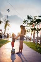 sorella che assiste il suo fratellino a cavalcare uno skateboard. foto