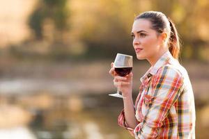premurosa giovane donna con bicchiere di vino foto