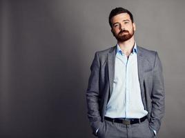 cool imprenditore in piedi su sfondo grigio foto