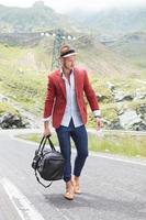 giovane uomo cammina con borsa sulla strada