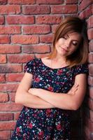 donna con le braccia conserte appoggiata al muro di rottura foto