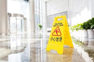 segno che mostra l'avvertenza di attenzione sul pavimento bagnato foto