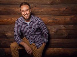 Ritratto di giovane uomo bello positivo contro il vecchio muro di legno. foto