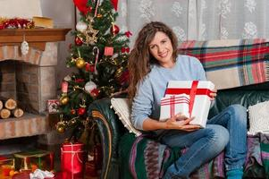 donna seduta sul divano tenendo presente di Natale foto
