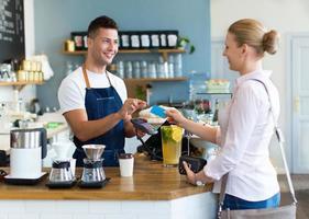 barista che serve il cliente nella caffetteria foto