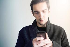 uomo vestito elegantemente utilizzando smartphone. foto