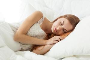 giovane donna che dorme nel letto foto
