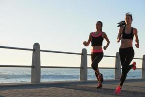due atleti di sesso femminile che eseguono dispositivo tracker fitness all'aperto