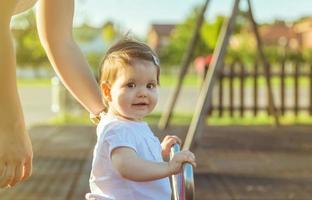 bambina che gioca su un'altalena altalena nel parco foto